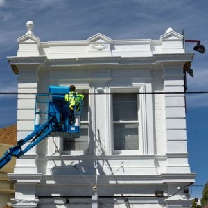 Our painters melbourne finishing an external white wall on a boom lift